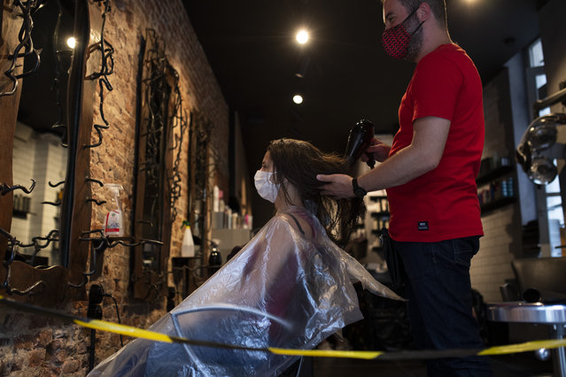 A woman, wearing a mask to protect against the spread of coronavirus, gets her hair styled in a hairdresser shop in downtown Brussels, Monday, July 27, 2020. Belgian Prime Minister Sophie Wilmes unveiled Monday a new set of drastic social distancing measures aimed at avoiding a new general lockdown amid a surge of COVID-19 infections. (Photo by Francisco Seco/AP Photo)