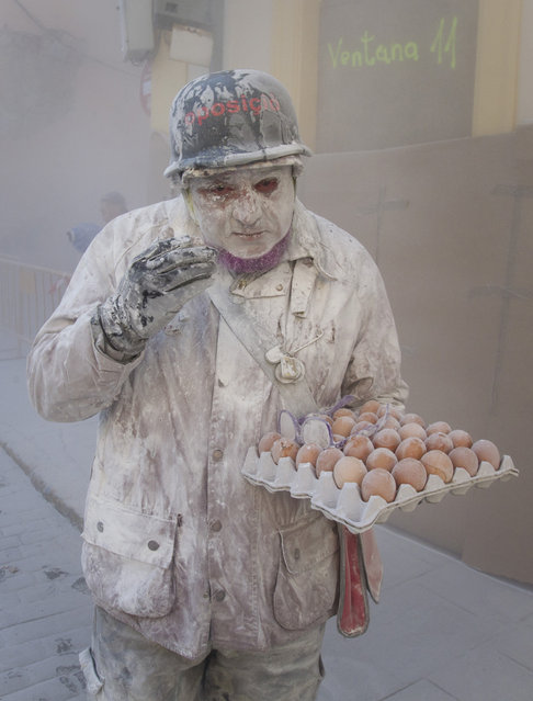 """A military dressed man holding eggs takes part in the battle of """"Enfarinats"""", a floor fight in the town of Ibi, in the south-eastern Spain on December 28, 2012. For 200 years Ibi's citizens annually celebrate with a battle using flour, eggs and firecrackers outside the city townhall. (Photo by Jaime Reina/AFP Photo)"""