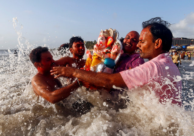 Devotees carry an idol of the Hindu god Ganesh, the deity of prosperity, into the Arabian Sea on the second day of Ganesh Chaturthi festival in in Mumbai, India, September 6, 2016. (Photo by Danish Siddiqui/Reuters)