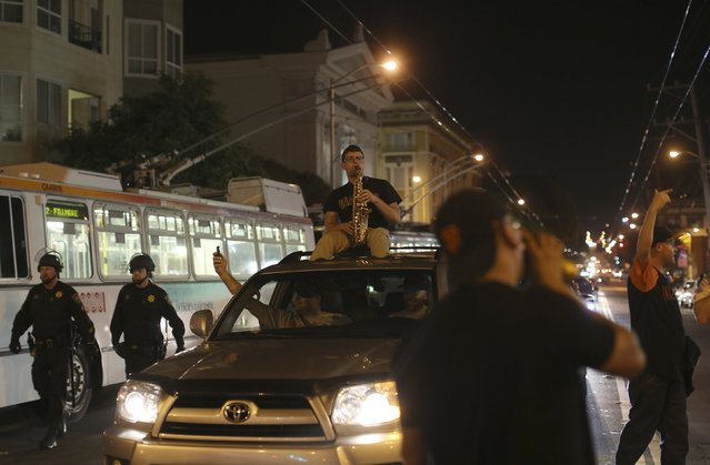 A man plays a saxophone atop a vehicle as fans celebrate in the Mission District after the San Francisco Giants defeated the Kansas City Royals in Game 7 of the World Series, in San Francisco, California October 29, 2014. (Photo by Robert Galbraith/Reuters)
