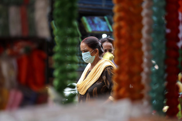 Women wearing face masks as a precaution against the coronavirus walk at market in Jammu, India, Thursday, August 6, 2020. India is the third hardest-hit country by the pandemic in the world after the United States and Brazil. (Photo by Channi Anand/AP Photo)