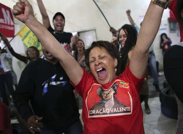 Members of Brazil's Movimento dos Sem-Teto (Roofless Movement) and supporters of Brazil's President and Workers' Party (PT) presidential candidate Dilma Rousseff, react to the first results of the Brazil general elections, inside the occupation of an empty building in downtown Sao Paulo, October 26, 2014. Rousseff is ahead of opposition candidate Aecio Neves in a nearly complete count of votes in Sunday's runoff election, according to the country's electoral authority. (Photo by Nacho Doce/Reuters)