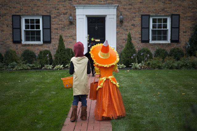 Kids dressed in costumes wait for candy while trick or treating during Halloween in Port Washington, New York, October 31, 2014. (Photo by Shannon Stapleton/Reuters)
