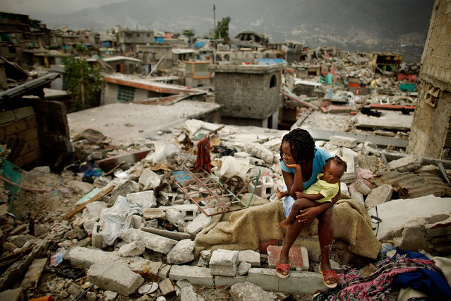 Sherider Anilus, 28, and her daughter, 9-month-old Monica, sit on the spot where her home collapsed during the January 12 earthquake in the Fort National neighborhood Feb. 26, 2010 in Port-au-Prince, Haiti. Living in a shack with her husband and two children, Anilus returned to Fort National from a tent camp in downtown Port-au-Prince so to escape the flash flooding that happens when it rains. (Photo by Chip Somodevilla/Getty Images)
