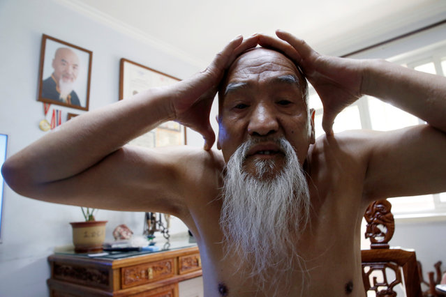 Kung Fu master Li Liangui moves his head through a space formed by his two hands as he demonstrates his Suogugong Kung Fu at his house in Beijing, China, May 5, 2016. (Photo by Kim Kyung-Hoon/Reuters)
