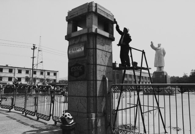A worker repairs a pillar in front of a statue of the late Chinese leader Mao Zedong in Yingkou, Liaoning province in 1994. (Photo by Reuters/China Daily)