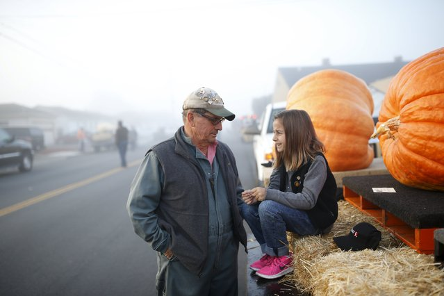 Farmer John (L) speaks with his granddaughter Delfina Bianchi, 7, as they wait next to their pumpkins during the annual Safeway World Championship Pumpkin Weigh-off in Half Moon Bay, California October 12, 2015. (Photo by Stephen Lam/Reuters)