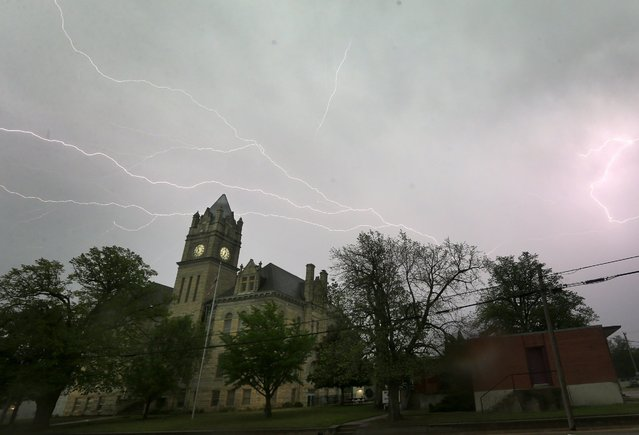 Lightning illuminates the sky over the Marion County Courthouse in Marion, Kan., Tuesday, April 26, 2016. Thunderstorms bearing hail as big as grapefruit and winds approaching hurricane strength lashed portions of the Great Plains on Tuesday. (Photo by Orlin Wagner/AP Photo)
