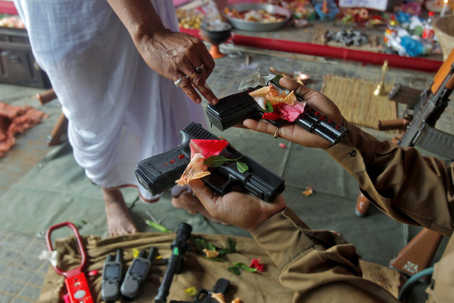 A police officer has weapons blessed by a Hindu priest during the Vishwakarma Puja festival on the outskirts of Agartala, India, September 17, 2016. (Photo by Jayanta Dey/Reuters)