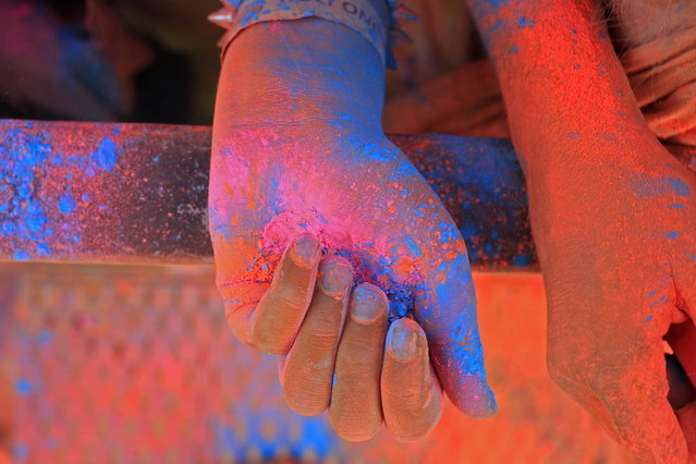A woman hands inside a cloud of paint powder next to her friend's during the holi one colour Festival held in the city of Cape Town, South Africa, Saturday, March 2, 2013. Thousands of people took part in the festival by throwing coloured paint powder at each other to express freedom and the colour of everyday life. (Photo by Schalk van Zuydam/AP Photo)
