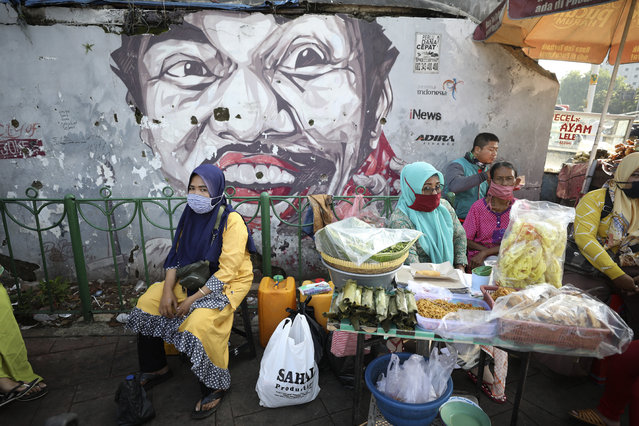 Indonesian women wearing masks as a precaution against the coronavirus outbreak sit at a food stall near a mural in Jakarta, Indonesia, Monday, September 21, 2020. (Photo by Dita Alangkara/AP Photo)