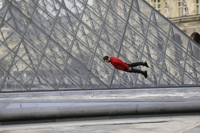 A man performs a jumps in the almost empty courtyard of the Louvre museum, Wednesday, October 14, 2020 in Paris. French President Emmanuel Macron is giving a nationally televised interview Wednesday night to speak about the virus, his first in months. French media reports say Macron will also step up efforts on social media to press the need for virus protections among young people. (Photo by Lewis Joly/AP Photo)