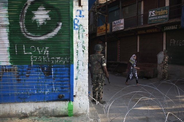 "A graffiti supporting Pakistan is seen on left as a Kashmiri girl walks past Indian paramilitary soldiers near a temporary check point in Srinagar, Indian controlled Kashmir, Thursday, September 29, 2016. Pakistan on Thursday said two of its soldiers were killed in an ""unprovoked"" attack when India fired across the border of the disputed region of Kashmir, while India said it had carried out a ""surgical strike"" against terrorists, in an exchange that marks an escalation in tensions between the uneasy and nuclear-armed neighbors. Pakistan and India often trade fire in Kashmir, a Himalayan region that is split between the two countries and claimed by both in its entirety. (Photo by Dar Yasin/AP Photo)"