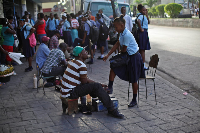 A girl gets her shoes polished before school in Port-au-Prince, Haiti, September 5, 2016. (Photo by Andres Martinez Casares/Reuters)