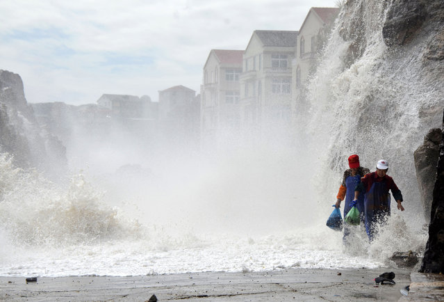 Residents make their way along a seaside street as waves surge past the coastline under the influence of Typhoon Danas in Wenling, Zhejiang province, October 8, 2013. (Photo by Reuters/China Daily)