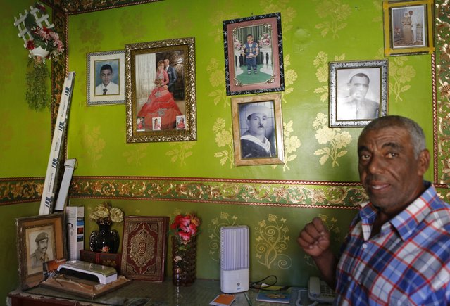 63-year-old fisherman El Hag Saleh shows family pictures inside his house in the fishermen's village in the El Max area of the Mediterranean city of Alexandria September 12, 2014. (Photo by Amr Abdallah Dalsh/Reuters)