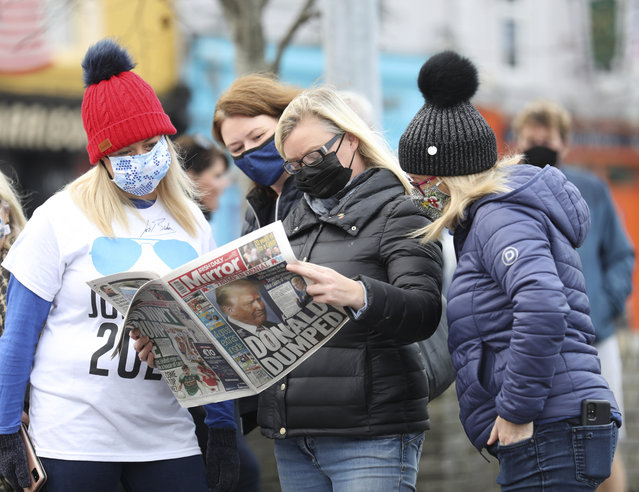 Residents read a copy of their local paper in the town of Ballina, North West of Ireland, the ancestral home of President elect Joe Biden, Saturday, November 7, 2020. Biden was elected Saturday as the 46th president of the United States, defeating President Donald Trump in an election that played out against the backdrop of a pandemic, its economic fallout and a national reckoning on racism. (Photo by Peter Morrison/AP Photo)