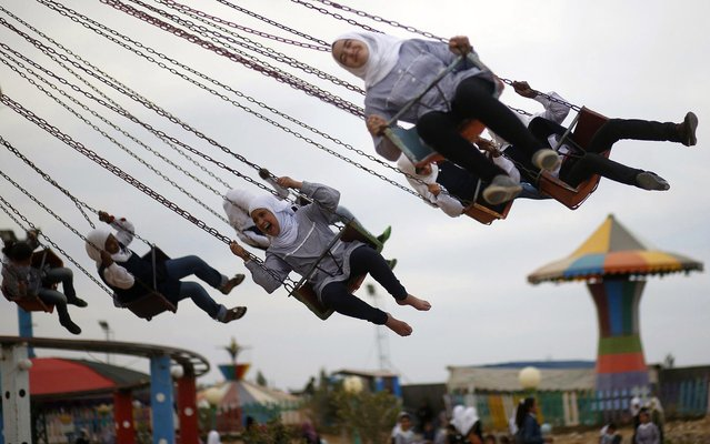 Palestinian girls have fun on a carousel amusement park built on land that was occupied by an Israeli camp in the central Gaza Strip, on April 11, 2013. (Photo by Mohammed Salem/Reuters)
