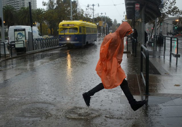 A pedestrian leaps over a rain puddle at the Embarcadero in San Francisco, California December 11, 2014. A Pacific storm lashed northern and central California on Thursday with heavy rain and high winds, knocking out electricity to tens of thousands of homes, disrupting commercial flights and prompting school closures in the San Francisco Bay area. (Photo by Robert Galbraith/Reuters)