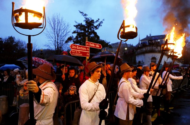 Torch carriers of the Compagnie 1602 take part in a procession in Geneva on December 14, 2014. (Photo by Pierre Albouy/Reuters)