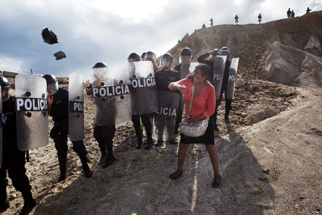 In this April 28, 2014 file photo, a woman throws a rock and a bag at police blocking her from getting home in the Huepetuhe district of the Madre de Dios region of Peru. Security forces began destroying illegal gold mining machinery in Peru's southeastern jungle region of Madre de Dios, as authorities began enforcing a ban on illegal mining. (Photo by Rodrigo Abd/AP Photo)