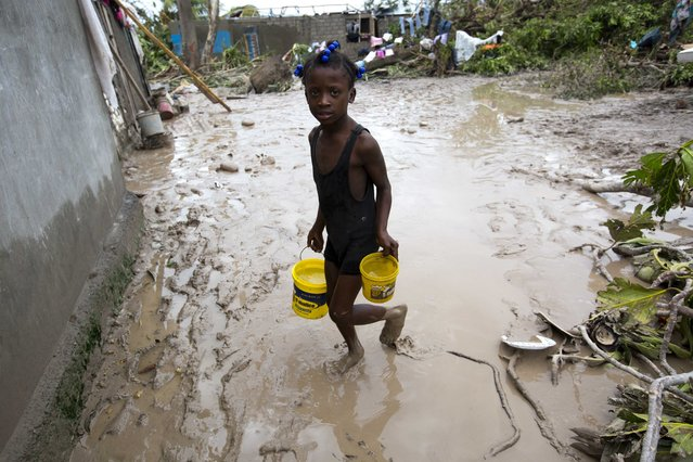 A girl lugs buckets of drinking water after the passing of Hurricane Matthew in Les Cayes, Haiti, Thursday, October 6, 2016. (Photo by Dieu Nalio Chery/AP Photo)