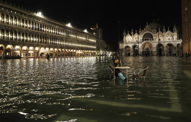 A woman sits in a flooded St. Mark's Square in Venice, Italy, Friday, March 30, 2018. High tides flooded Venice, leading Venetians and tourists to don high boots and use wooden walkways to cross the square and other areas under water. (Photo by Antonio Calanni/AP Photo)