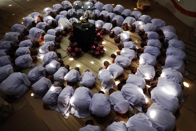 Novice nuns pray at the Sathira-Dhammasathan Buddhist meditation centre in Bangkok April 21, 2013. A group of Thai girls are choosing to spend part of their school holidays as Buddhist nuns, down to having their heads shaven at the meditation centre. The centre, founded in 1987, is a learning community for peace and harmony that has programs open to people regardless of age and gender. (Photo by Damir Sagolj/Reuters)