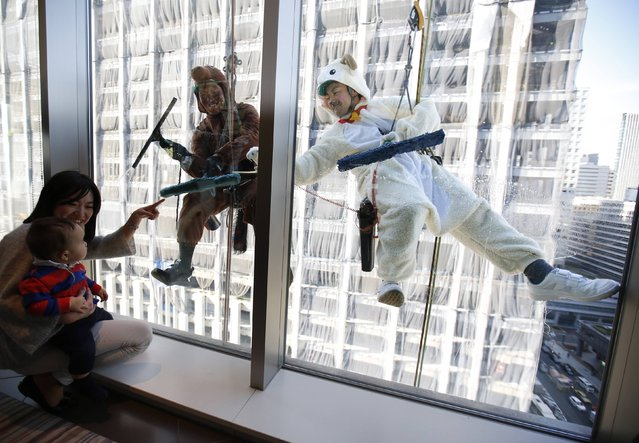 People look at window cleaners, dressed in horse and sheep (R) costumes featuring animal signs from the Chinese zodiac calendar, work during an event promoting the year-end and new year at a hotel in the business district of Tokyo December 19, 2014. The year of 2014 is the year of the horse and 2015 is the year of the sheep according to the Chinese zodiac calendar. (Photo by Issei Kato/Reuters)