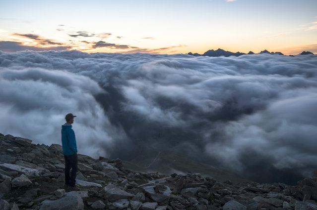A tourist the sunrise above a sea of fog on Eggishorn mountain (2927 meters over sea level), in Fiesch, Switzerland, early Tuesday, July 28, 2015. (Photo by Dominic Steinmann/Keystone via AP Photo)