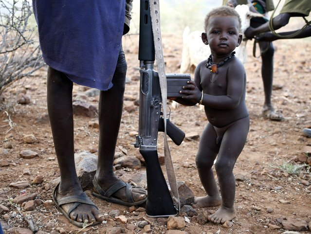 A Turkana boy holds on to his father's rifle in a village inside the Turkana region of the Ilemi Triangle, northwest Kenya December 21, 2014. The Ilemi Triangle is a disputed region in East Africa, claimed by South Sudan and Kenya, bordering also Ethiopia. The dispute arose from unclear wording of a 1914 treaty which tried to allow free movement of the Turkana people, nomadic herders who had traditionally grazed the area. (Photo by Goran Tomasevic/Reuters)