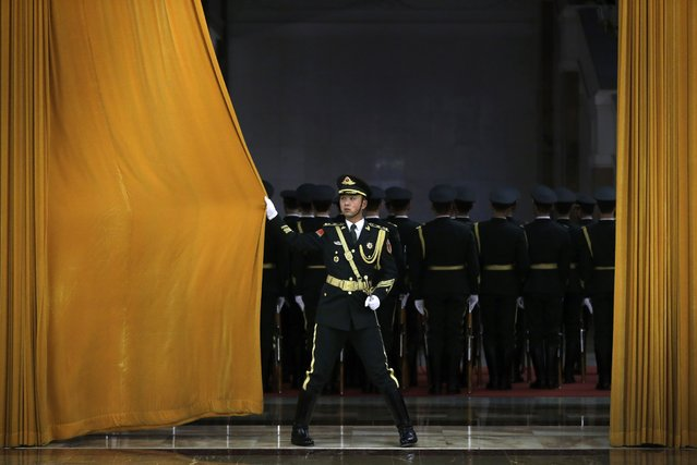 A Chinese People's Liberation Army soldier closes a curtain after members of honor guard rehearse for a welcome ceremony held by Chinese President Xi Jinping for visiting Egyptian President Abdel-Fattah el-Sissi at the Great Hall of the People in Beijing, China Tuesday, December 23, 2014. (Photo by Andy Wong/AP Photo)