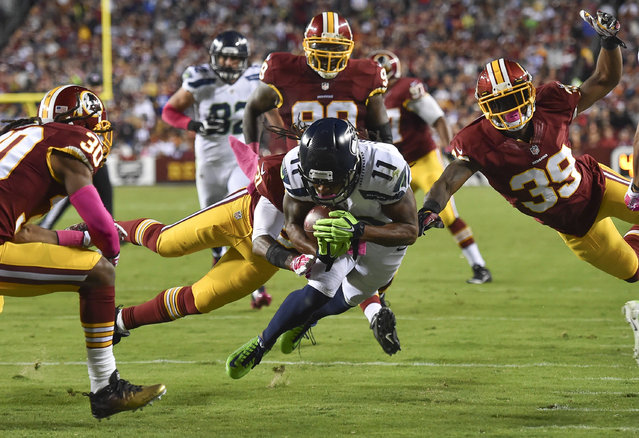 Seattle Seahawks wide receiver Percy Harvin (11) dives for a touchdown through Redskins defenders in the second quarter during a game between the Seattle Seahawks and the Washington Redskins at FedEx Field on October 6, 2014 in Landover, Md. The touchdown was called back for a penalty. (Photo by Ricky Carioti/The Washington Post)