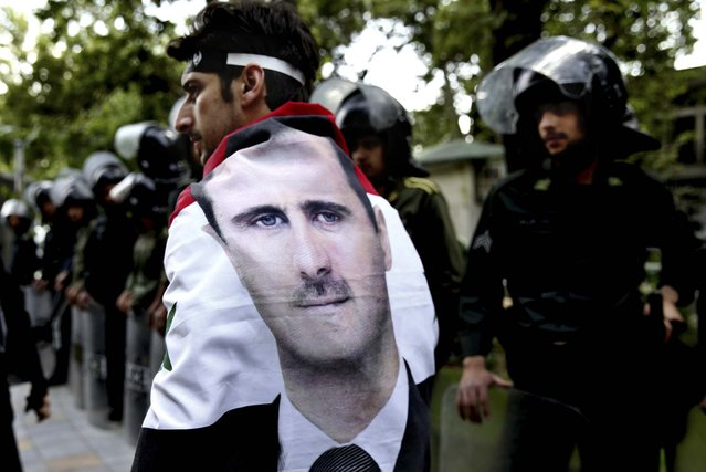A man wrapped in a Syrian flag with a portrait of President Bashar Assad, walks past riot police at an anti-Israeli demonstration in front of the UN office in Tehran, on May 6, 2013. Iran condemns Israeli Air strikes on Syria and urged countries in the region to stand against the attack. (Photo by Ebrahim Noroozi/Associated Press)