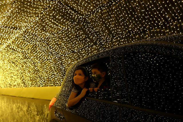 Children look at lights from inside their family car as they visit Luminna Fest, a drive-through Christmas light festival, in Sao Paulo, Brazil on December 5, 2020. (Photo by Amanda Perobelli/Reuters)