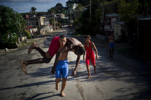 """In this January 22, 2018 photo, young wrestlers train in the street during the week-long student wrestling championship coined """"The truth of my neighborhood"""", organized by locals in the Chicharrones neighborhood of Santiago, Cuba. In this neighborhood, a wrestling-loving local man created a homegrown, neighborhood-backed program to support aspiring wrestlers from Cuba's economically struggling provinces. (Photo by Ramon Espinosa/AP Photo)"""