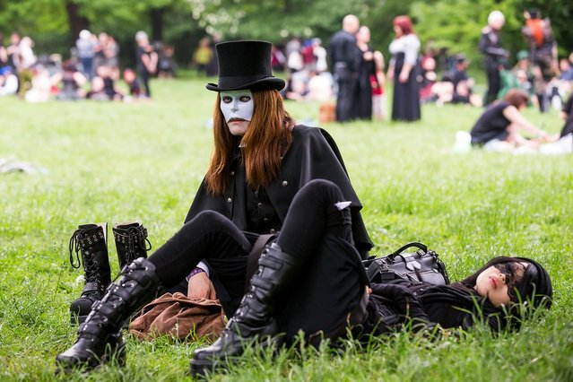 A goth couple wearing masks rest on the lawn during the traditional park picnic on the first day of the annual Wave-Gotik Treffen, or Wave and Goth Festival, on May 17, 2013 in Leipzig, Germany. The four-day festival, in which elaborate fashion is a must, brings together over 20,000 Wave, Goth and steam punk enthusiasts from all over the world for concerts, readings, films, a Middle Ages market and workshops. (Photo by Marco Prosch)