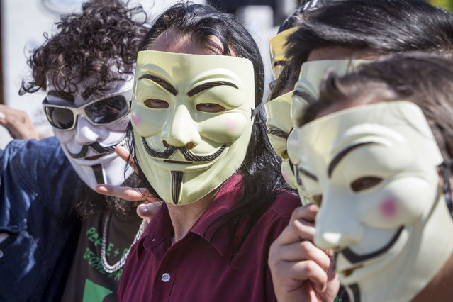 Australia: Anonymous activists meet in inner Brisbane wearing Guy Fawkes masks, an item that has been banned during the G20 Summit, ahead of the Peoples' March on November 14, 2014 in Brisbane, Australia. The Peoples' March is expected to be one of the largest protests during the summit. (Photo by Glenn Hunt/Getty Images)
