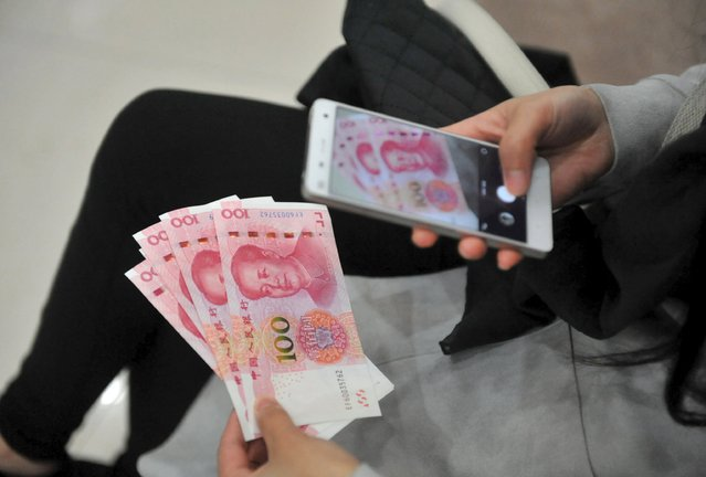 A woman takes pictures of new 100 yuan banknotes she withdrew from a bank in Hangzhou, Zhejiang province, China, November 12, 2015. (Photo by Reuters/Stringer)
