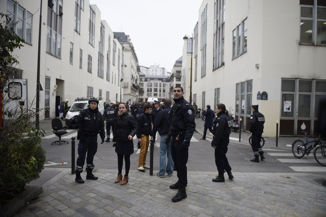 Police forces gather in street outside the offices of the French satirical newspaper Charlie Hebdo in Paris on January 7, 2015, after armed gunmen stormed the offices leaving at least 10 people dead according to prosecutors. (Photo by Martin Bureau/AFP Photo)