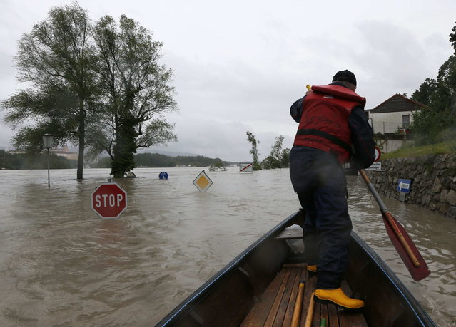 A member of the emergency services travels by boat along a flooded street in the centre of the Austrian village of Emmersdorf, about 100 km (62 miles) west of Vienna June 3, 2013. Torrential rain in Tyrol, Salzburg, Upper and Lower Austria caused heavy flooding over the weekend, forcing people to evacuate their homes. (Photo by Leonhard Foeger/Reuters)