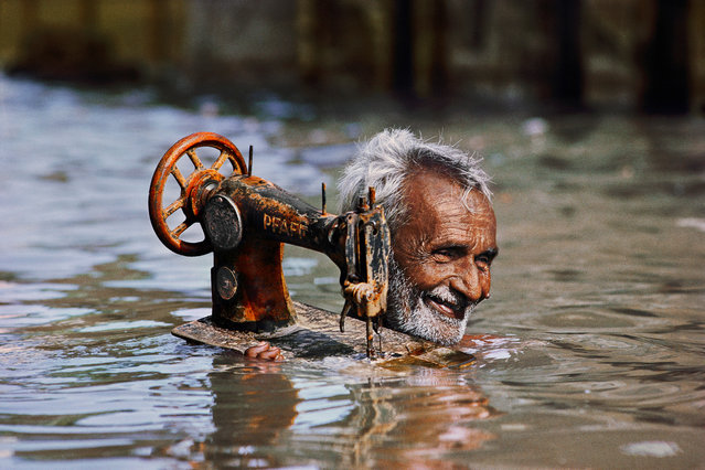 A tailor carries his sewing machine through monsoon waters, Porbandar, Gujarat, 1983. (Photo by Steve McCurry)