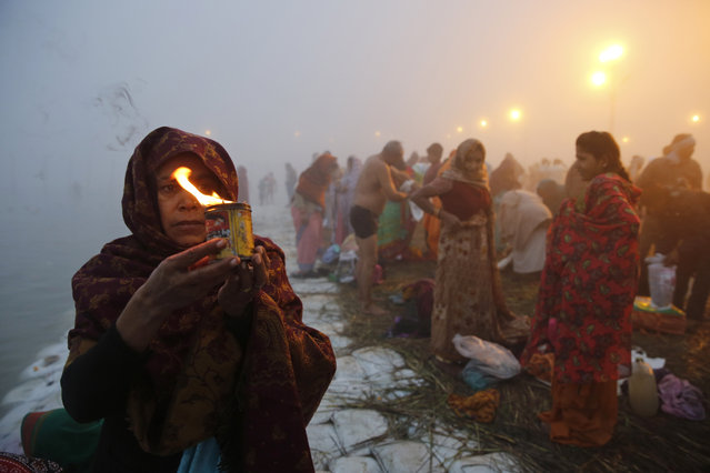 "A Hindu devotee offers prayers after a holy dip at Sangam, the confluence of rivers Ganges and Yamuna, on Makar Sankranti festival during the annual traditional fair of ""Magh Mela"" in Allahabad, India, Wednesday, January 14, 2015. (Photo by Rajesh Kumar Singh/AP Photo)"