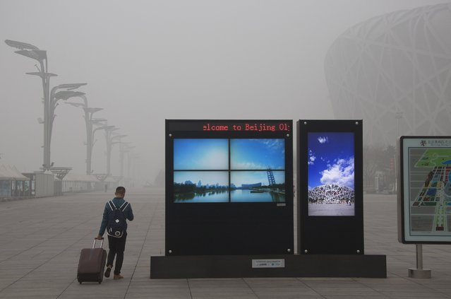 A man pulls his luggage past electronic screens showing the Olympic Green park under blue skies, near the National Stadium (R), or the Bird's Nest, amid heavy smog in Beijing, China, December 1, 2015. (Photo by Reuters/China Daily)