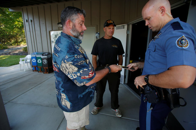 Joseph Rice (L), of the Josephine County Oath Keepers, which later disbanded and became the Liberty Watch of Josephine County, gives a U.S. Constitution to a Oregon State Police officer after a town hall meeting with U.S. Senator Ronald Lee Wyden in Grants Pass, Oregon, U.S. May 28, 2016. (Photo by Jim Urquhart/Reuters)
