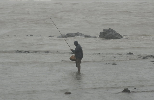 An Indian angler fishes on the sea front during heavy rain showers in Mumbai on June 18, 2013. The monsoon, which India's farming sector depends on, covers the subcontinent from June to September, usually bringing some flooding. But the heavy rains arrived early this year, catching many by surprise. The country has received 68 percent more rain than normal for this time of year, data from the India Meteorological Department shows. (Photo by Punit Paranjpe/AFP Photo)