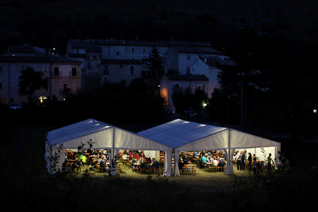 People eat underneath a temporary tent during a fair organised every year to attempt to boost the economy of the town of Santo Stefano di Sessanio in the province of L'Aquila in Abruzzo, inside the national park of the Gran Sasso e Monti della Laga, Italy, September 3, 2016. (Photo by Siegfried Modola/Reuters)