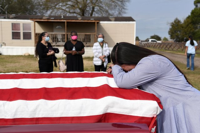 Lila Blanks holds the casket of her husband, Gregory Dwayne Blanks, who died of COVID-19, ahead of his funeral in San Felipe, Texas, January 26, 2021. Greg died on January 17 at the age of 50. The father of 7 served in the U.S. Army and later built a career as an HVAC technician. (Photo by Callaghan O'Hare/Reuters)
