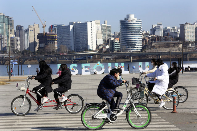 Young people wearing face masks to help protect against the spread of the coronavirus ride bicycles at a park in Seoul, South Korea, Sunday, January 24, 2021. (Photo by Ahn Young-joon/AP Photo)
