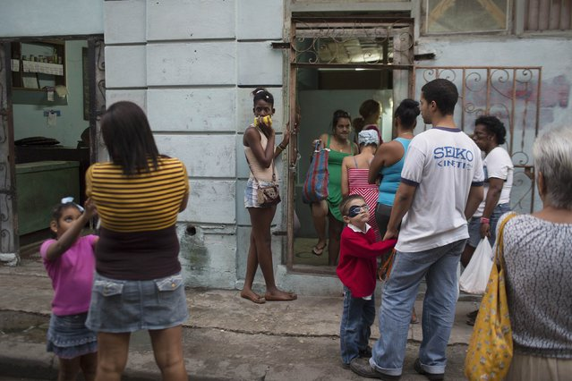 """People line up to enter a subsidised state store, or """"bodega"""", where Cubans can buy basic products with a ration book they receive annually from the government, in downtown Havana, January 20, 2015. (Photo by Alexandre Meneghini/Reuters)"""
